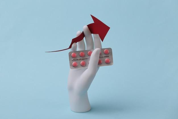 La mano bianca del manichino tiene una freccia di crescita verso l'alto con vesciche di pillole su sfondo blu. il business medico aumenta il prezzo dei farmaci