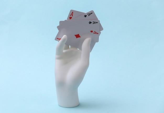 La mano bianca del manichino con quattro assi si erge su sfondo blu. poker, gioco di carte