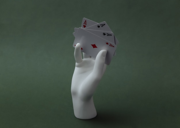La mano bianca del manichino con quattro assi si erge su sfondo verde. poker, gioco di carte