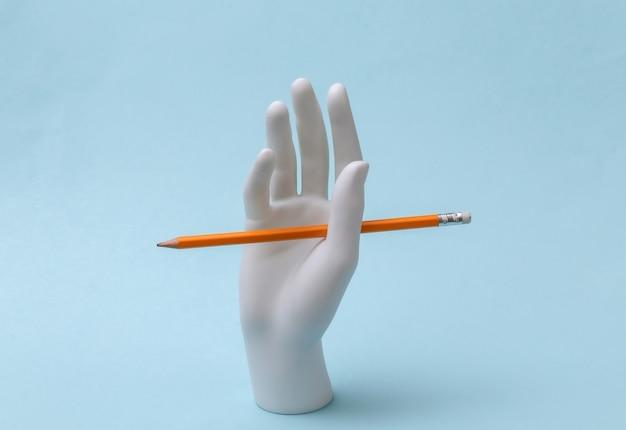 La mano bianca del manichino con la matita sta su fondo blu. conoscenza, concetto di educazione