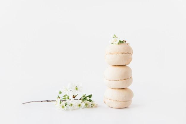 I marshmallow bianchi si impilano con un fiore bianco sopra e altri accanto su sfondo bianco white