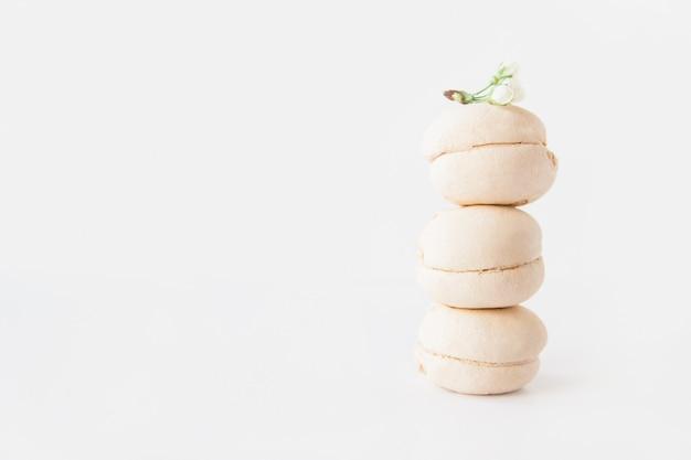 I marshmallow bianchi si impilano con un fiore bianco in cima su sfondo bianco