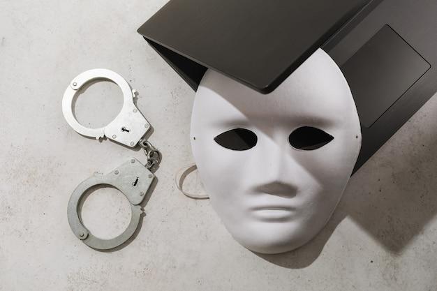 Maschera bianca su un laptop e manette sul tavolo il concetto sul tema dei crimini e dell'anonimato nel campo della tecnologia dell'informazione