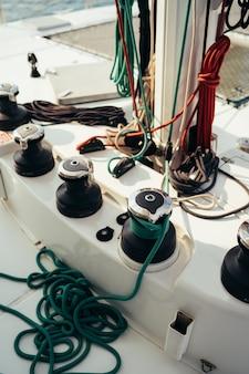 Albero bianco di una barca a vela con drizze del verricello e cavi colorati