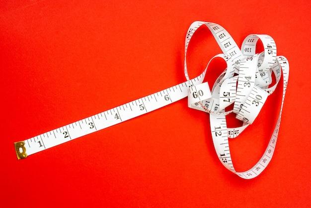 Nastro di misurazione bianco su sfondo rosso. misura della lunghezza e della circonferenza. perdere peso e ingrassare.
