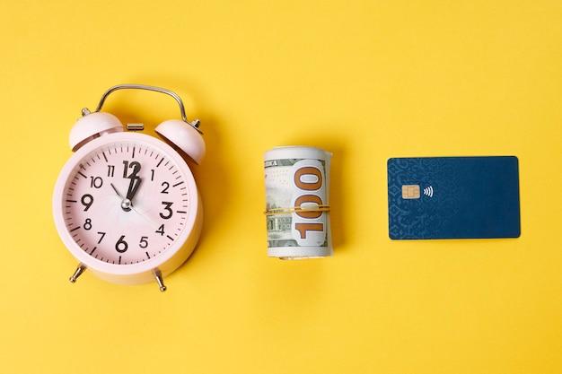 Sveglia meccanica bianca rotolo di dollari e carta di credito blu