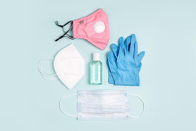 Maschere mediche bianche e respiratori con guanti, disinfettante per le mani su sfondo blu. protezione maschera facciale kn95 o n95 e maschere chirurgiche per protezione virus, influenza, coronavirus, covid-19.