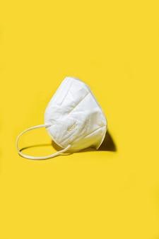 Maschera respiratore medico kn95 bianco con ombra su un colore giallo brillante
