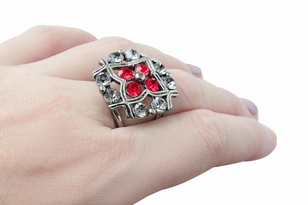 Anello in metallo bianco con pietre rosse e trasparenti su mano umana dalla pelle bianca, primo piano