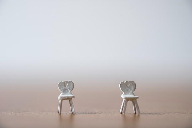La sedia in miniatura bianca mantiene le distanze pubbliche e previene l'infezione da pandemia da diffusione di virus corona covid-19. concetto di allontanamento sociale.
