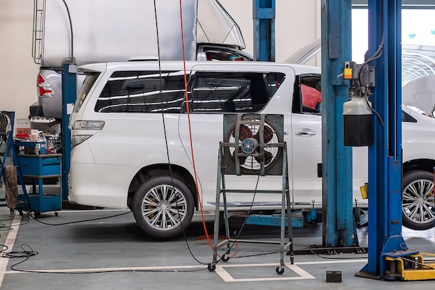 Un minivan bianco è su una piattaforma di sollevamento auto per la riparazione in un negozio del centro di assistenza auto, riparazione auto