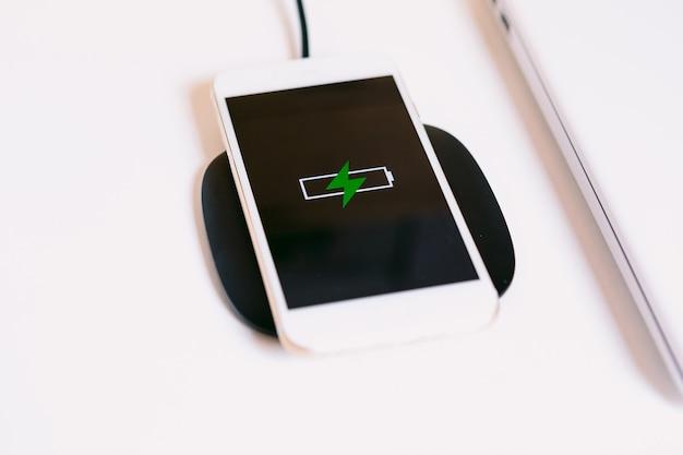 Smartphone mobile bianco con il logo di una batteria con un fulmine verde sullo schermo, in carica su una base di ricarica senza cavo accanto al laptop su un tavolo da lavoro bianco