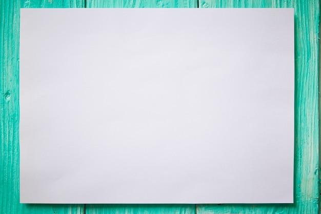 Carta bianca mockup bianca su fondo di legno verde.