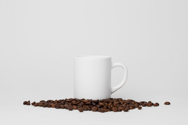 Tazza bianca sulla disposizione dei chicchi di caffè
