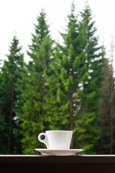 La tazza bianca di caffè caldo scuro del mattino sulla staccionata in legno con la foresta.