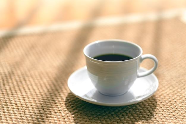 Una tazza bianca di caffè caldo sul pavimento della moquette