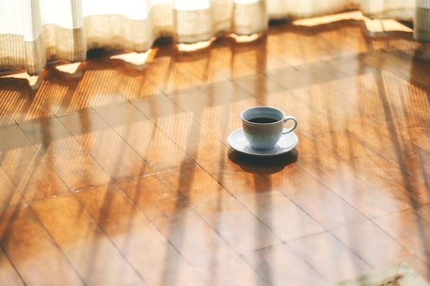 Una tazza bianca di caffè caldo sul pavimento di legno vicino alla tenda in casa