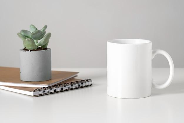 Mockup di tazza bianca sul tavolo in interni minimalisti, concetto di affari, succulente e taccuini.