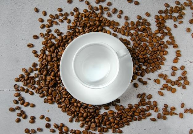 Tazza bianca con piattino per bevande calde su fondo neutro