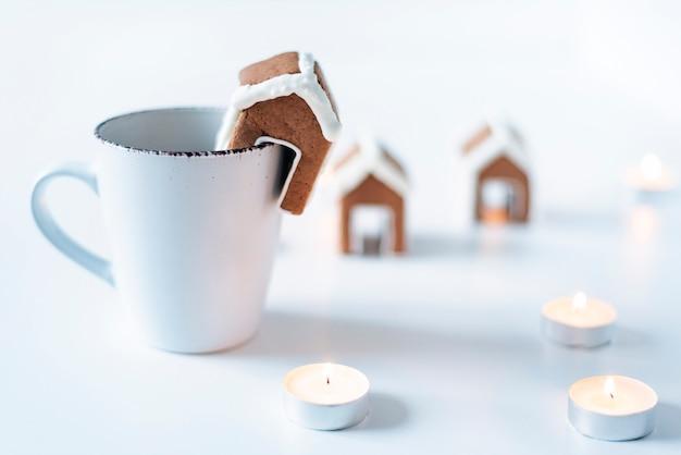 Tazza bianca, piccola casa di marzapane e candele. modello di biscotto di panpepato.