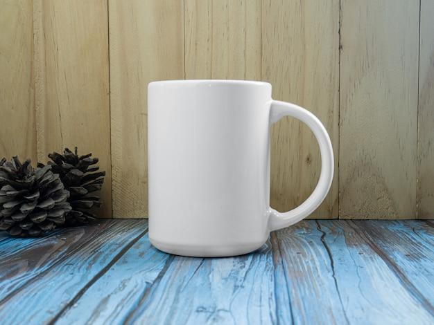 La tazza bianca sul legno del tavolo per mockup o sfondo