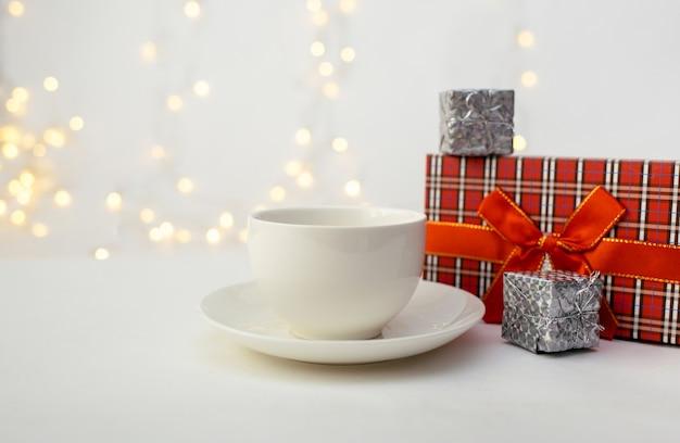 Una tazza bianca con un piattino e una confezione regalo su uno sfondo bianco con un bokeh con un posto per il testo