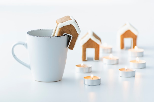 Tazza bianca con tè, piccola casa di pan di zenzero e candele. vacanze di natale accoglienti.