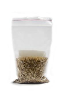Semi di senape bianca per la germinazione in sacchetto isolato su una superficie bianca.