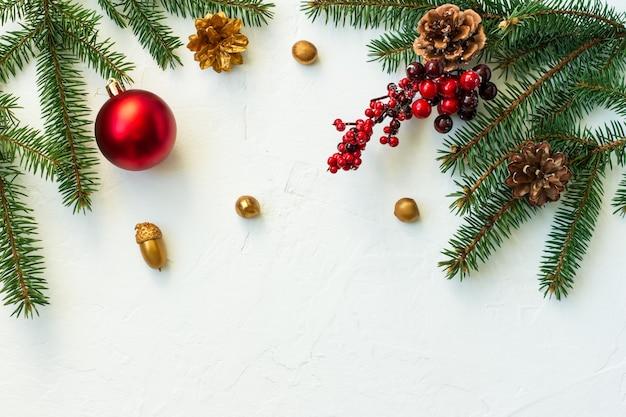 Sfondo bianco di capodanno con rami di abete rosso, palline rosse e bacche, noci dorate e ghiande. vista dall'alto. una copia dello spazio.