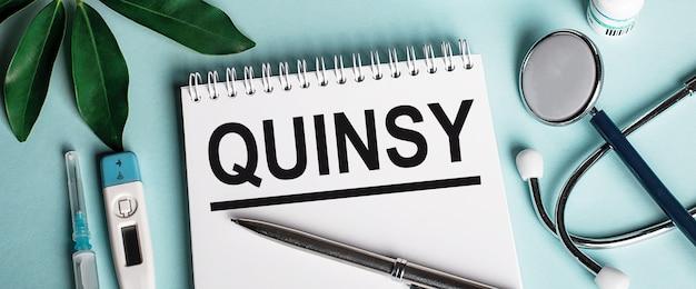 In un quaderno bianco su sfondo blu, vicino a un foglio di pastori, uno stetoscopio, una siringa e un termometro elettronico, è scritta la parola quinsy