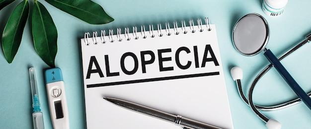 In un taccuino bianco su una superficie blu, vicino a un foglio di pastori, uno stetoscopio, una siringa e un termometro elettronico, è scritta la parola alopecia