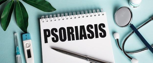 In un quaderno bianco su una superficie blu, vicino a un foglio di pastori, uno stetoscopio, una siringa e un termometro elettronico, è scritta la parola psoriasi. concetto medico