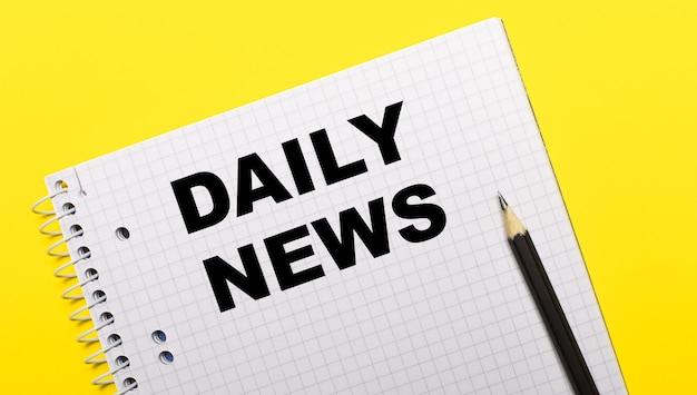 Taccuino bianco con notizie giornaliere scritte a matita nera su sfondo giallo brillante.