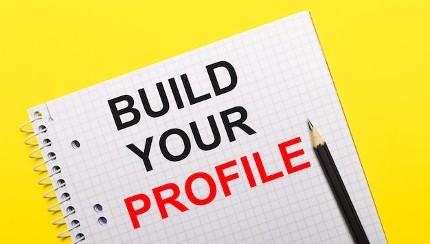 Quaderno bianco con scritta costruisci il tuo profilo scritta a matita nera su sfondo giallo brillante.