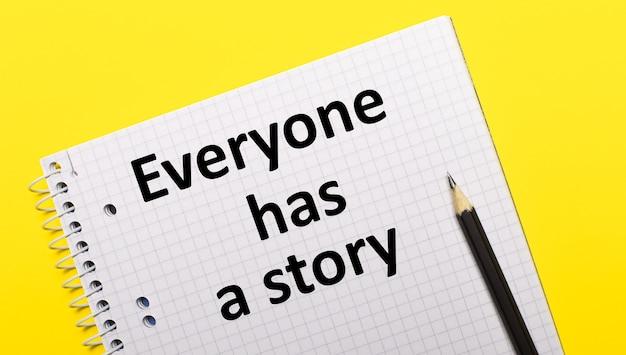 Quaderno bianco con scritta everyone has a story scritta a matita nera su una superficie gialla brillante.