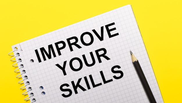Taccuino bianco con scritta migliora le tue competenze scritta a matita nera su sfondo giallo brillante.