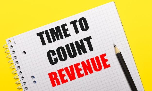 Quaderno bianco con la scritta time to count revenue scritta a matita nera su sfondo giallo brillante.