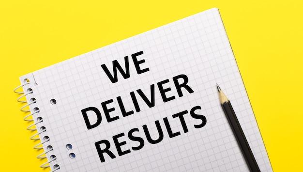 Taccuino bianco con scritta consegniamo risultati scritti a matita nera su sfondo giallo brillante