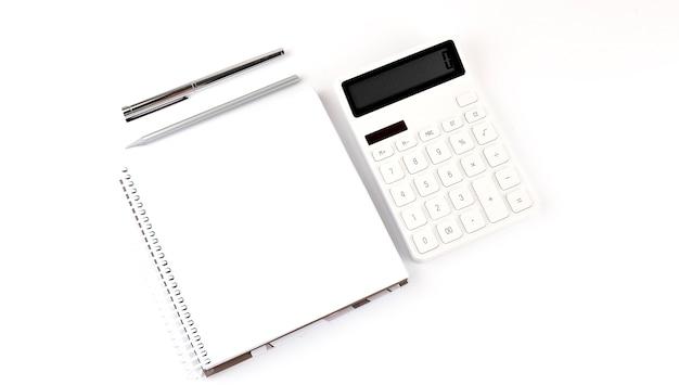 Taccuino bianco con una matita, una penna e una calcolatrice su sfondo bianco
