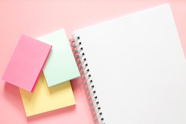 Quaderno bianco con spirale e tre adesivi multicolori su un delicato rosa