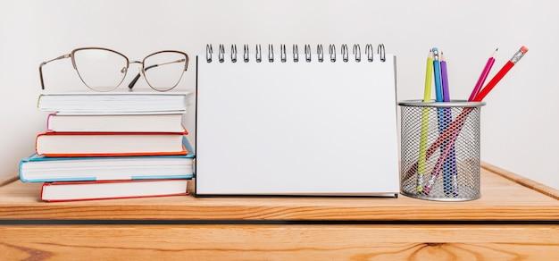 Blocco note bianco, libri, bicchieri e pensil sul posto di lavoro