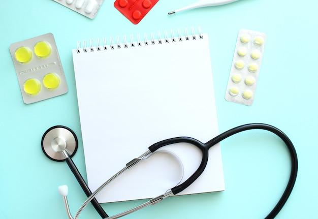 Blocco note bianco che si trova accanto allo stetoscopio e alle pillole su sfondo blu. concetto medico