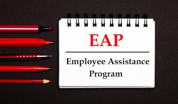 Un blocco note bianco con il testo eap employee assistance program, scritto su un blocco note bianco accanto a penne rosse, matite e pennarelli su una superficie nera Foto Premium