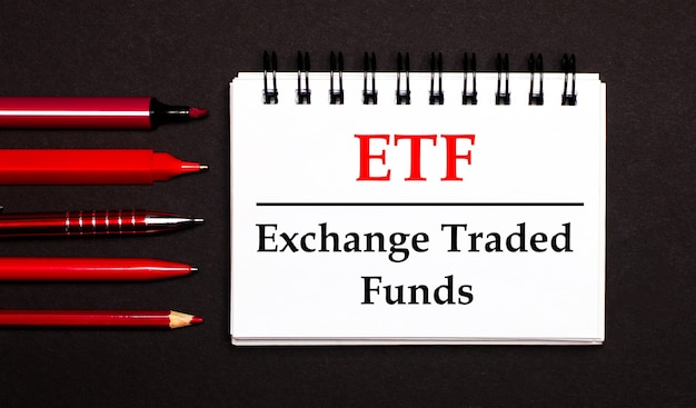 Un blocco note bianco con il testo etf exchange traded funds, scritto su un blocco note bianco accanto a penne rosse, matite e pennarelli su sfondo nero