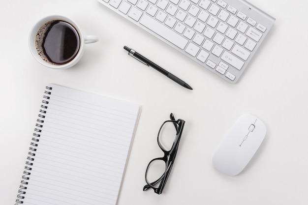 Tavolo scrivania da ufficio bianco con taccuino in bianco, tastiera del computer e altre forniture per ufficio.