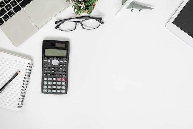 Scrivania da ufficio bianca. tavolo con taccuino vuoto, tablet, calcolatrice, computer e altre forniture per ufficio