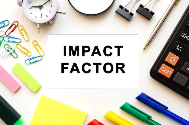 Tavolo scrivania da ufficio bianco con calcolatrice, lente d'ingrandimento, penne colorate e altri articoli di cancelleria. testo sulla scheda impact factor. vista dall'alto. concetto di affari.