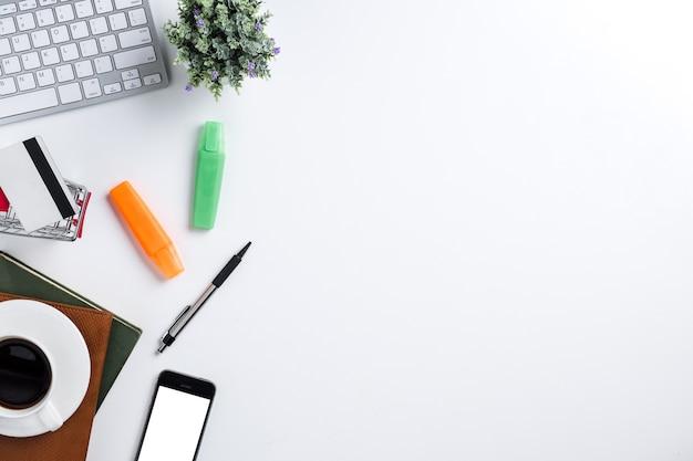 Scrivania bianca con tastiera di computer, notebook e forniture