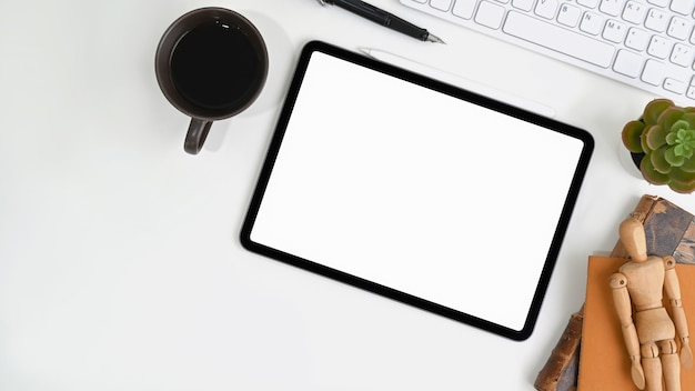 Scrivania da ufficio bianca con tavoletta digitale, tazza di caffè, tastiera e cactus.