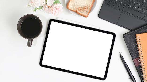 Scrivania da ufficio bianca con tavoletta digitale, notebook, pane e tazza di caffè.